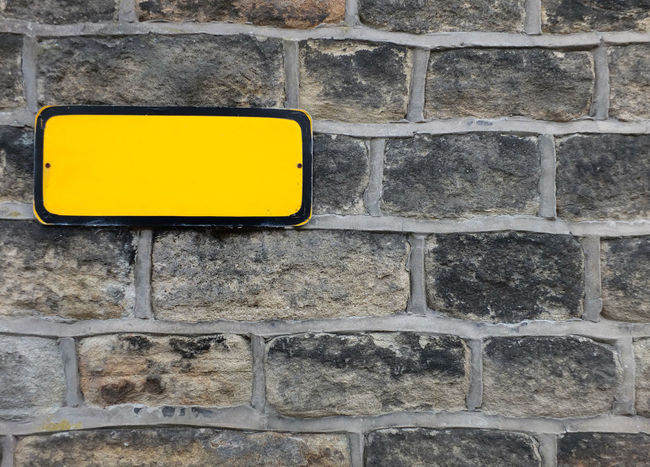 A blank yellow metal sign on a stone wall Blank Sign Stone Wall Yellow Wall Architecture Brick Wall Outdoors Sign Full Frame Backgrounds Communication Copy Space Blank Rectangle Brick