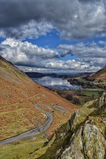 Scenic view of mountains by ullswater against cloudy sky