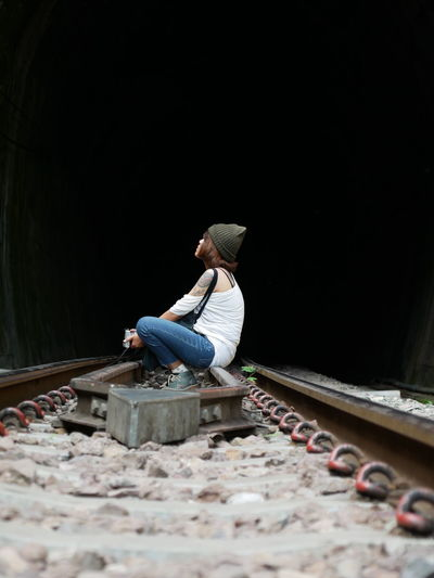 Full length of woman sitting on railroad track by tunnel