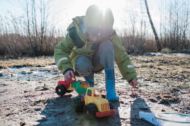Boy playing with toy car on field during winter