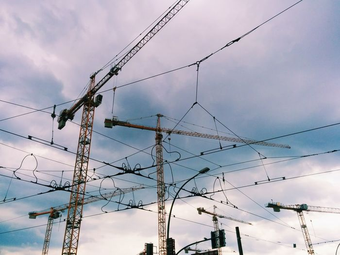 Low Angle View Of Cranes And Cables Against Cloudy Sky