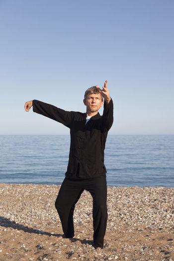 Full Length Of Man Exercising At Beach Against Clear Sky