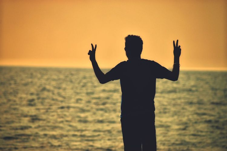 Silhouette Man Gesturing Peace Sign At Beach Against Clear Orange Sky