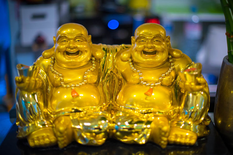 Budai Boudhisme Representation Art And Craft Sculpture Statue Human Representation Gold Colored Indoors  Male Likeness Creativity No People Focus On Foreground Close-up Figurine  Craft Still Life Yellow Table Selective Focus Belief Temptation