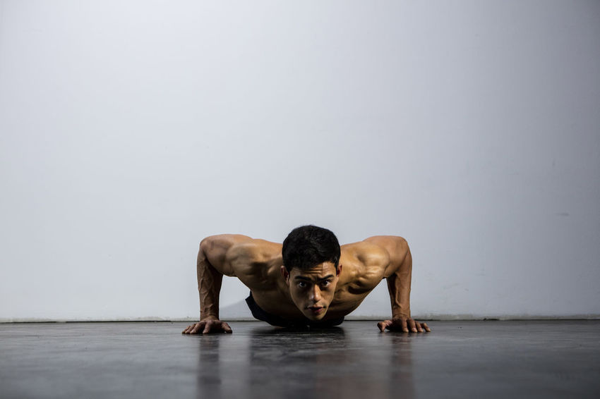 A fitness model performing push ups. Front facing. Adult Asian  Athlete Body & Fitness Exercise Human Body Man Nam Vo Shirtless Sportsman Deltoid  Detemination Fitness Model Grey Wall Handsome Hunk Male Muscle Muscular Build One Person Push Ups Strength Training Strong Studio Shot Torso
