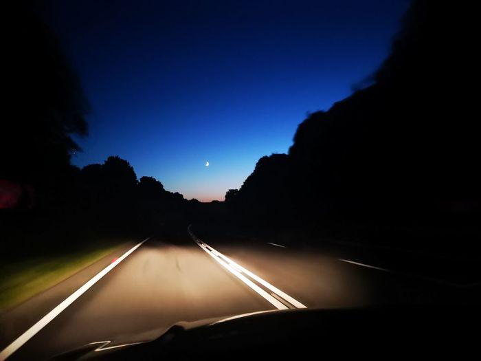 Road seen through car windshield at night