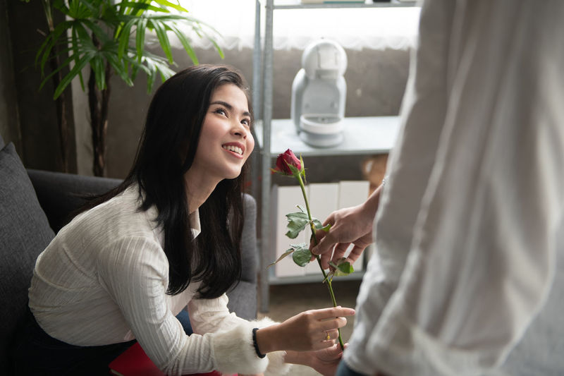 Picture of young man surprising woman with flowers Holding Young Adult Women Casual Clothing Two People Lifestyles Adult Young Women Smiling Day Leisure Activity Real People People Indoors  Emotion Waist Up Side View Beautiful Woman Love Giving Rose - Flower Valentine's Day  Flirting Dating Romantic
