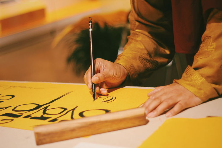 Midsection of man writing on yellow paper