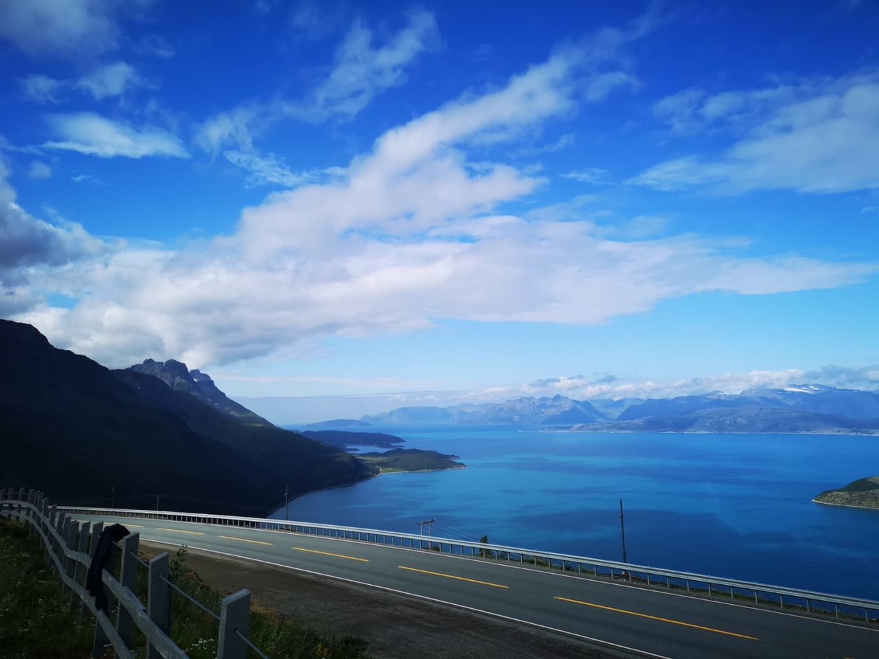 mountain, sky, cloud - sky, scenics - nature, beauty in nature, transportation, road, mountain range, water, nature, non-urban scene, blue, tranquil scene, railing, tranquility, sea, no people, day, mode of transportation, outdoors, crash barrier