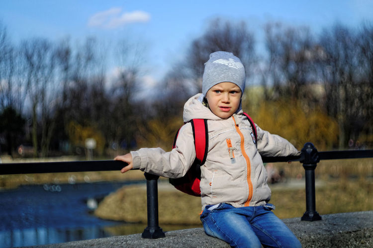 Boy relaxing on retaining wall