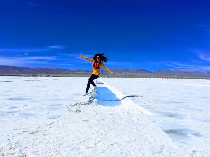 Full Length Of Woman Jumping On Salt Flat