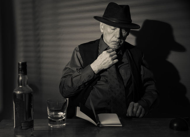 Film Noir reloaded: The dirty old detective in his bureau talking to a new client Acting Adult Hat Alcohol Bottle Day Detective Front View Hat Indoors  Mature Men Monochrome Old Person Old Person Sitting One Man Only One Person People Real People Sitting Studio Shot Table