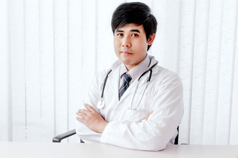 Portrait Of Doctor With Stethoscope Sitting In Hospital