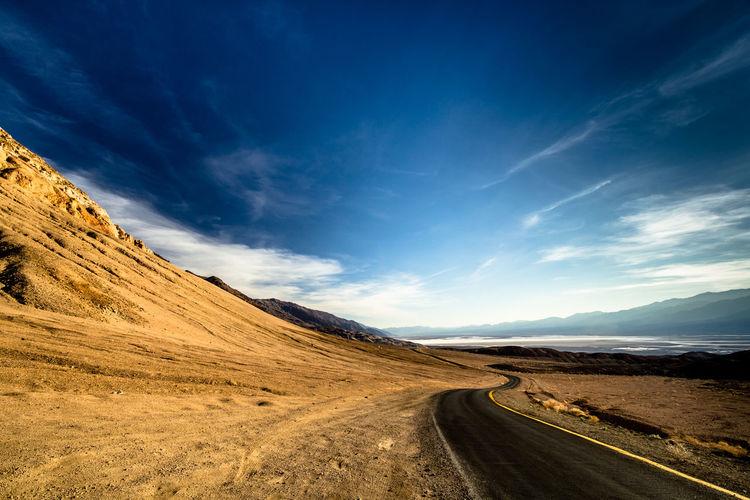 Road Leading Towards Landscape Against Blue Sky