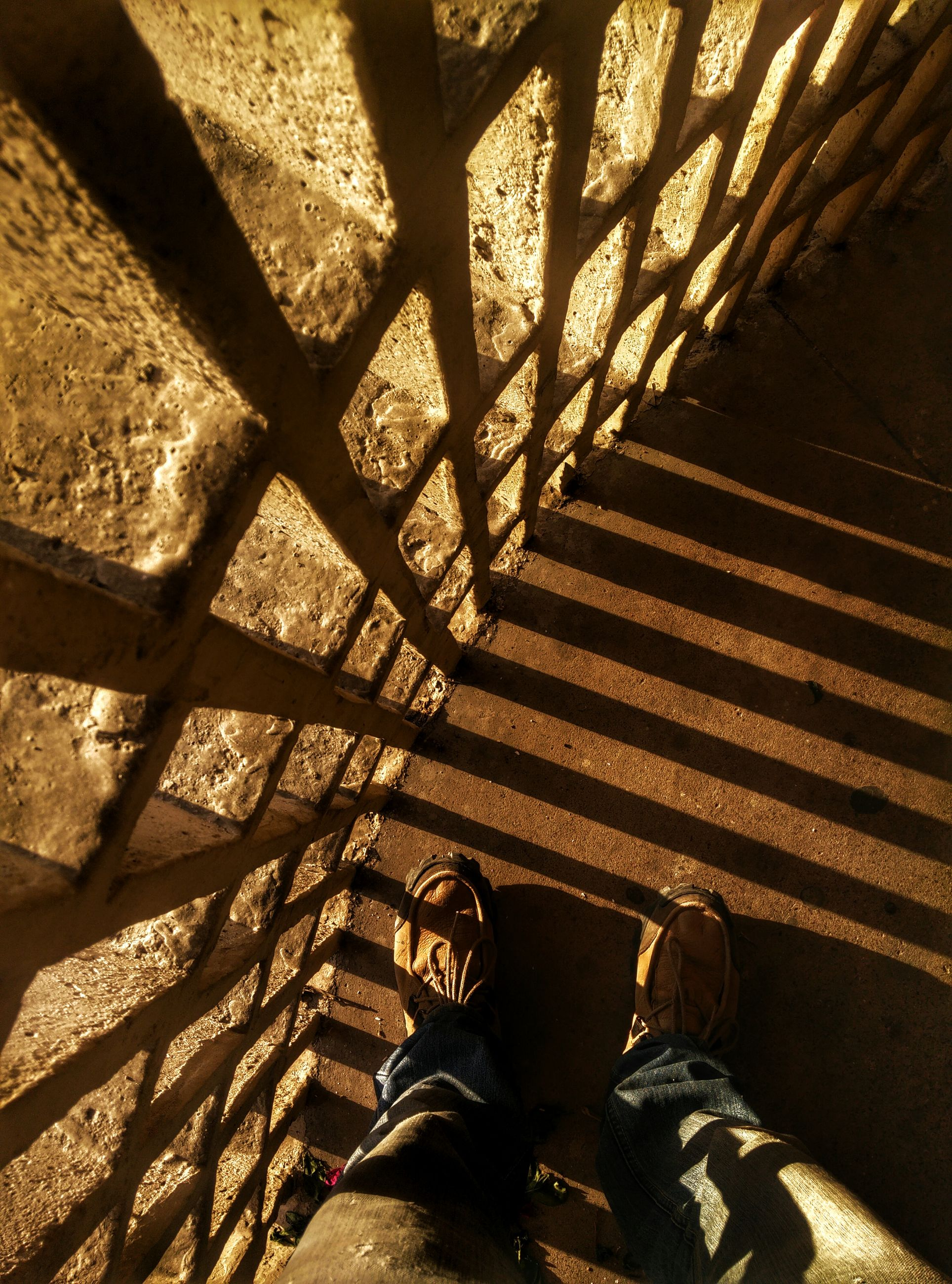 low section, person, personal perspective, shoe, standing, lifestyles, men, high angle view, human foot, leisure activity, shadow, unrecognizable person, sunlight, steps, indoors, footwear