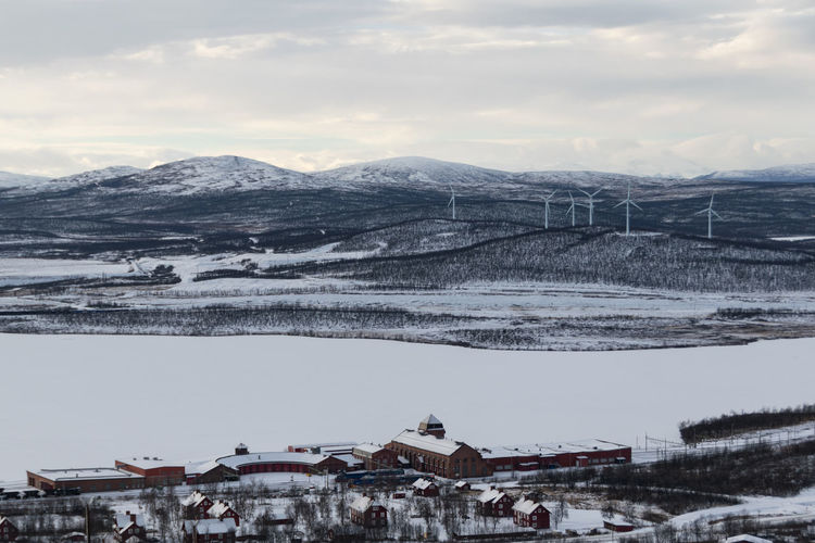 High angle view of town and wind turbines against sky in winter.