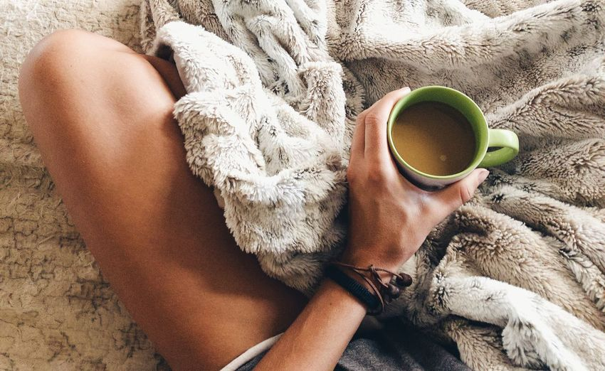 Midsection Of Woman Having Coffee On Bed