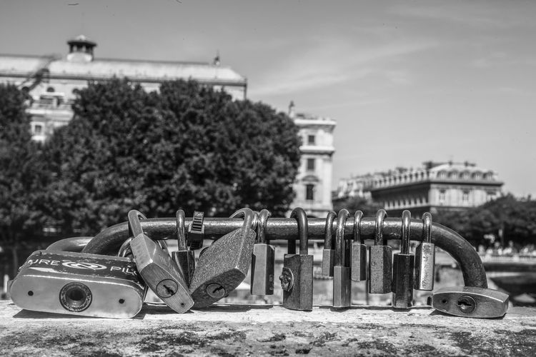 Close-up of padlocks attached to railing in city
