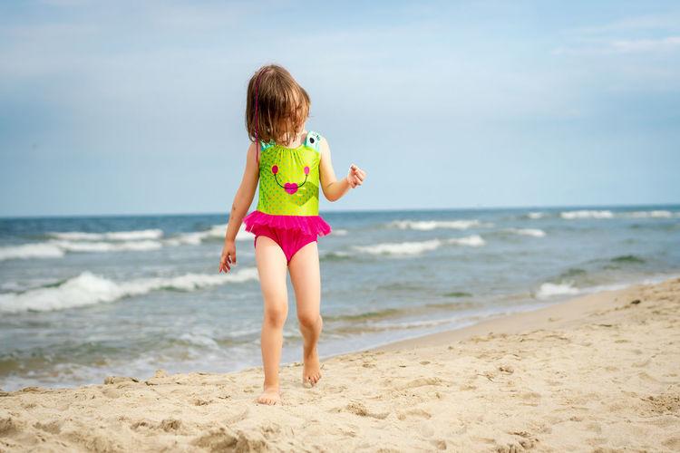 Full length of girl walking at beach against sky