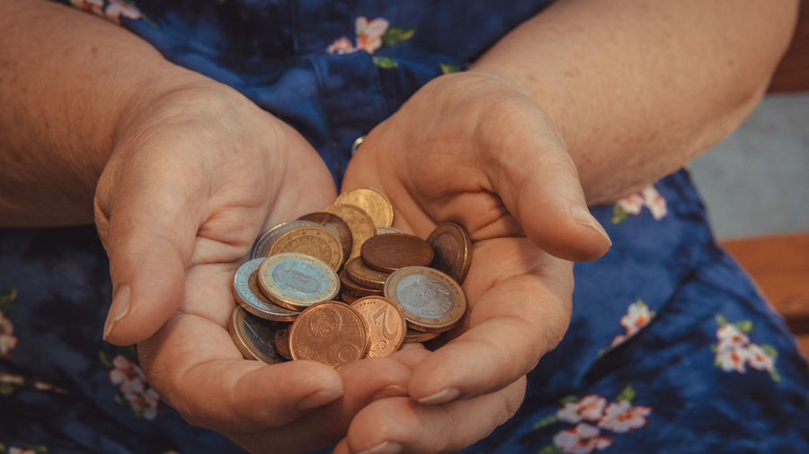 Midsection of person holding coins
