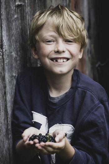 Portrait of happy boy holding blueberries