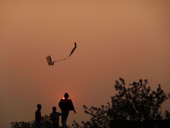 Family flying kite against orange sky during sunset