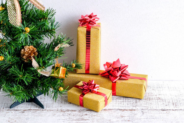 Close-up of christmas tree and presents against wall