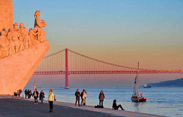 sunset at Padrao Architecture Bridge - Man Made Structure Day Outdoors Padrão Dos Descobrimentos People Sky Sunset Sunset At Padrão Dos Descobrimentos Travel Destinations