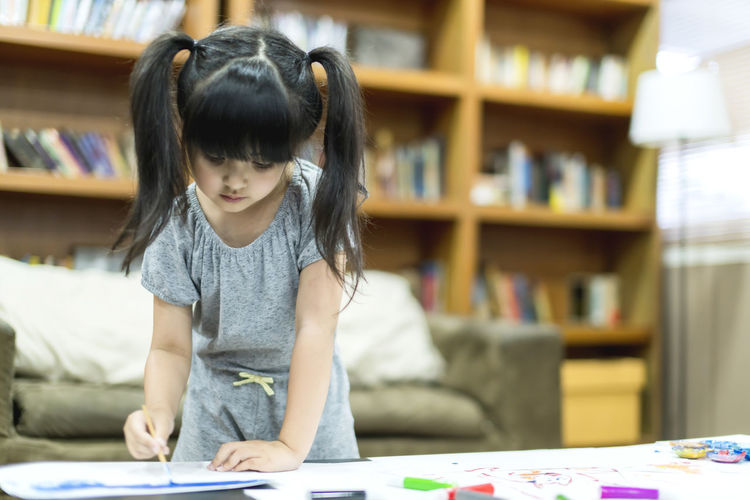 Girl painting over paper on table