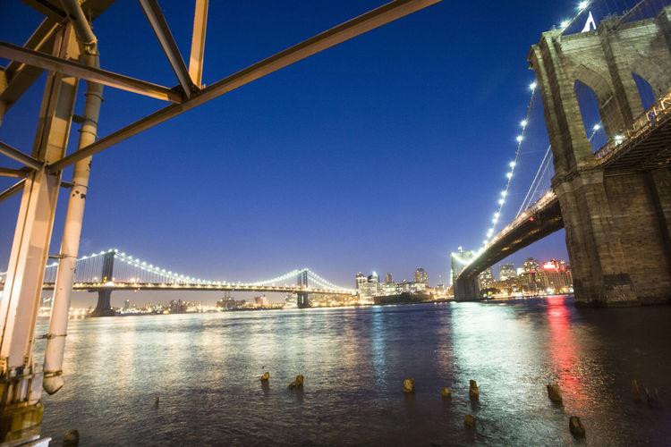 Illuminated bridge over river against blue sky in city