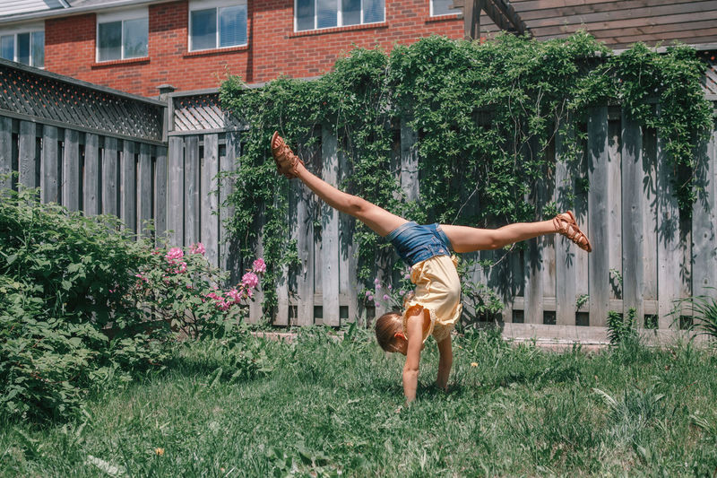 Full length of girl doing handstand against plants in yard