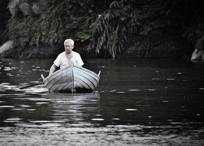 Serene People Portrait Tranquil Scene Water Travel Tranquility Silence Rowing Floating On Water Outdoors Idyllic Lake Beauty In Nature Senior Adult Adventure