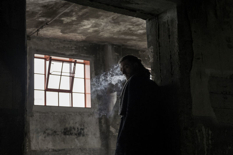 Man Smoking In Abandoned Building