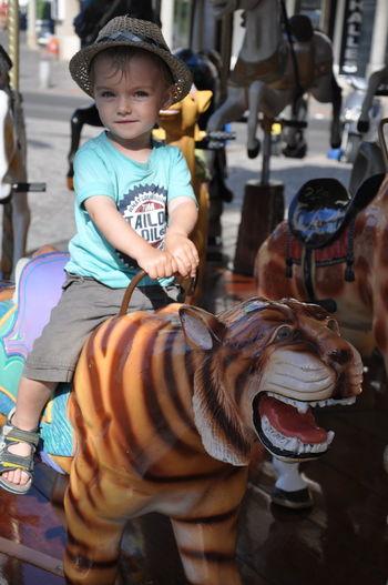 Full length portrait of boy sitting on carousel tiger in amusement park