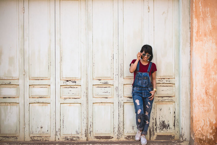 Full length of woman with sunglasses standing against wall