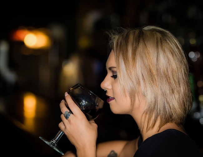 Side view of woman drinking wine at bar