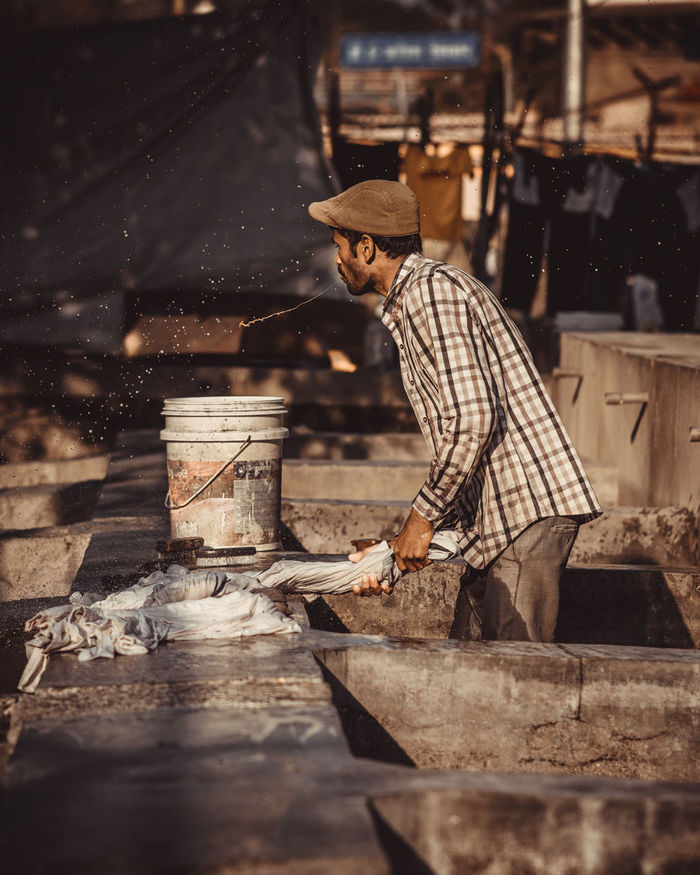 SIDE VIEW OF MAN WORKING ON GRILL