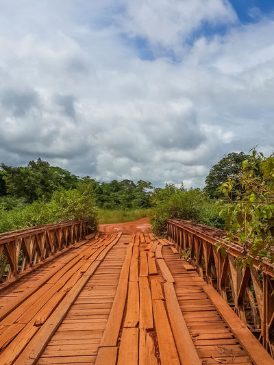 Dodgy red stained wooden bridge with timber planks and old iron rails crossing river in Gabon, Central Africa Improvisation Road Africa Beauty In Nature Bridge Bridge - Man Made Structure Built Structure Cloud - Sky Day Gabon Growth Nature No People Outdoors Plant Scenics Simple Simplicity Sky The Way Forward Tree Tropical Wood - Material
