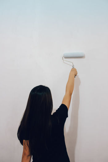 Rear view of woman painting wall with paint roller