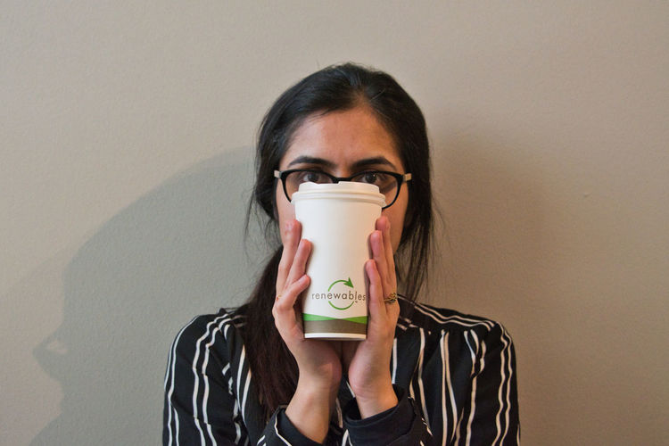 Portrait of woman holding coffee cup against wall