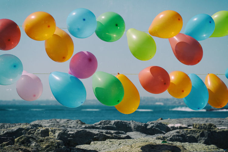 Multi colored balloons on rocks by sea against sky