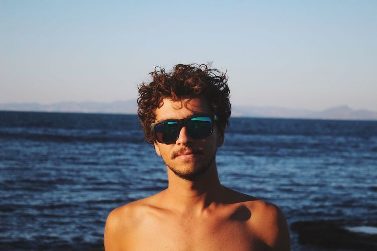 Portrait of young man wearing sunglasses at beach against sky