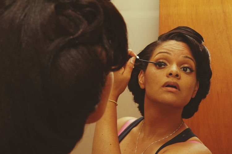 Close-Up Of A Woman Applying Mascara In Mirror