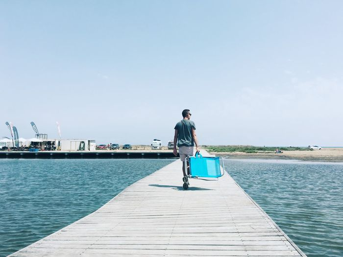 Young man with a beach chair on a pier in Delta del Ebro, Spain Sky Boardwalk Summertime Summer Ebro Ebro River Delta Full Length Sea Day Pier Nature Scenics - Nature Outdoors Copy Space Casual Clothing Beauty In Nature