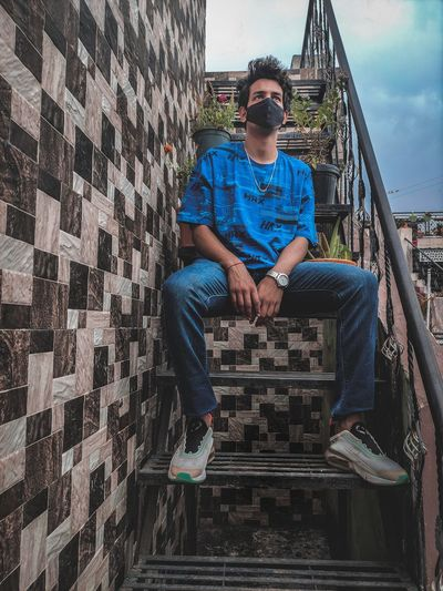 Full length of man sitting on wall