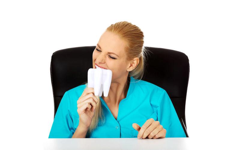 Nurse biting dentures against white background