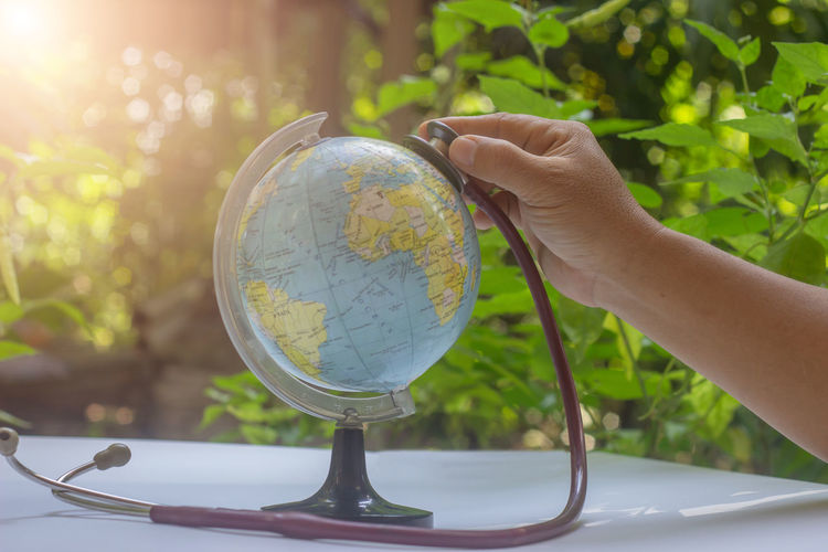 Cropped hand examining globe