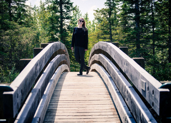Full length of young woman standing against trees on footbridge
