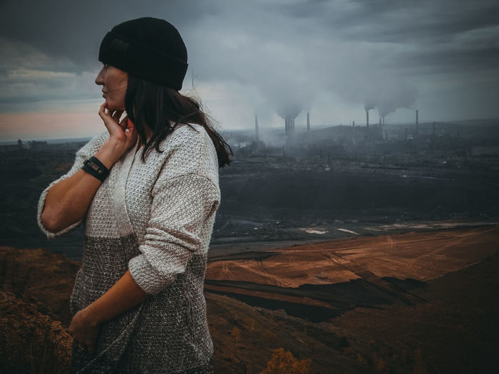 Thoughtful woman looking away while standing against factory emitting smoke