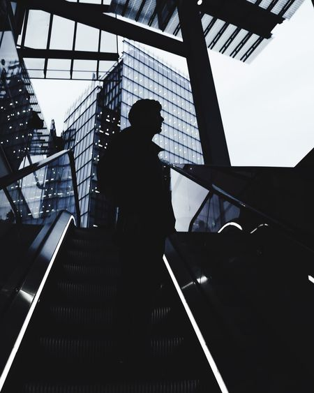 Silhouette Of Man Standing On Escalator